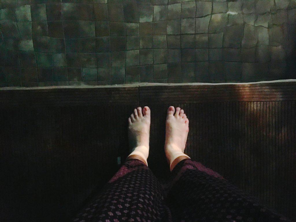 インフィニティプールの浅瀬に足を浸けている様子を撮影した写真