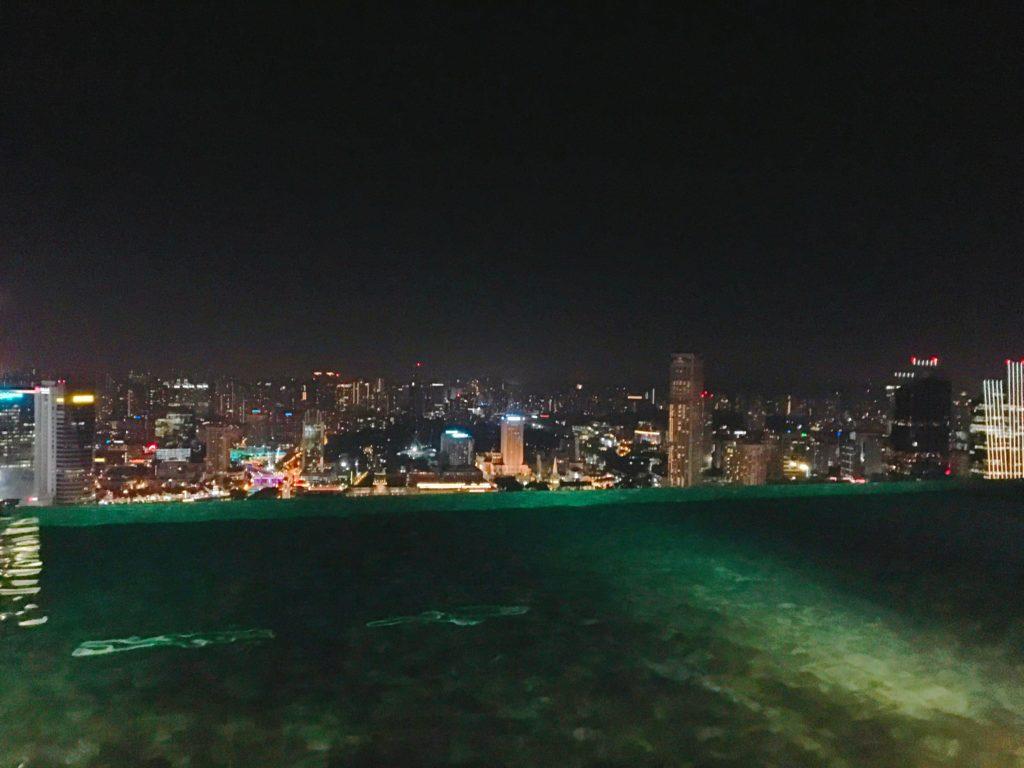 インフィニティプールの奥にシンガポールの夜景が広がっている様子を撮影した写真