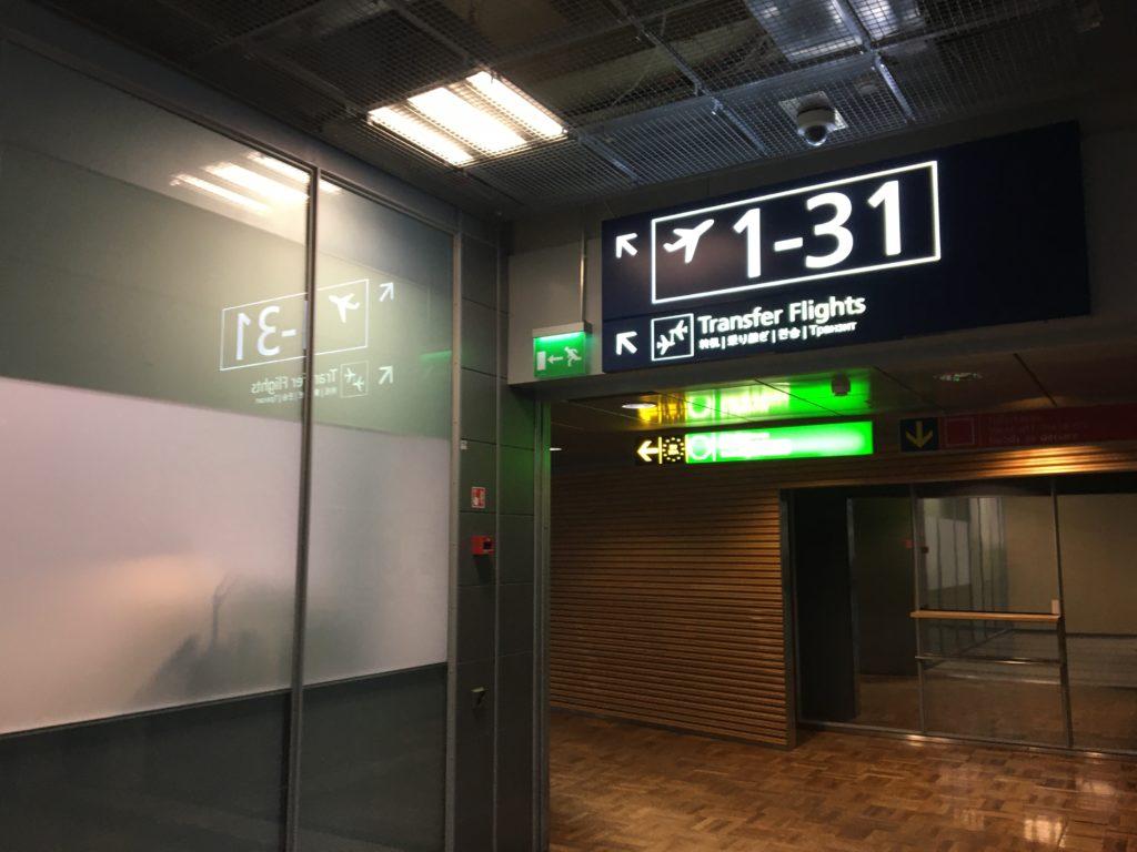 私が実際にヘルシンキ・ヴァンター国際空港で目印にした、1-31番ゲートの方向を示す案内板(このガラス扉奥側が税関申告の場所)を撮影した写真