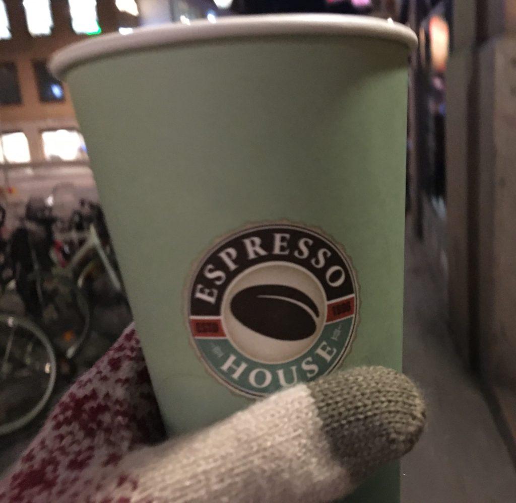 ストックホルムで手袋をしてテイクアウトコーヒーを持っている様子を撮影した写真