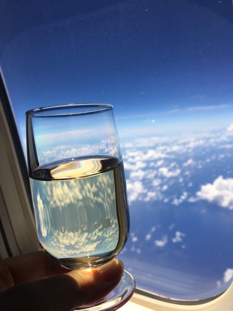 私が頂いた白ワインのグラスに綺麗な空模様が反射している様子を撮影した写真