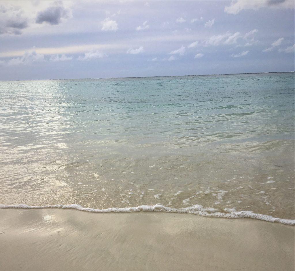 さらさらの砂浜に透明な波が押し寄せている様子を撮影した写真