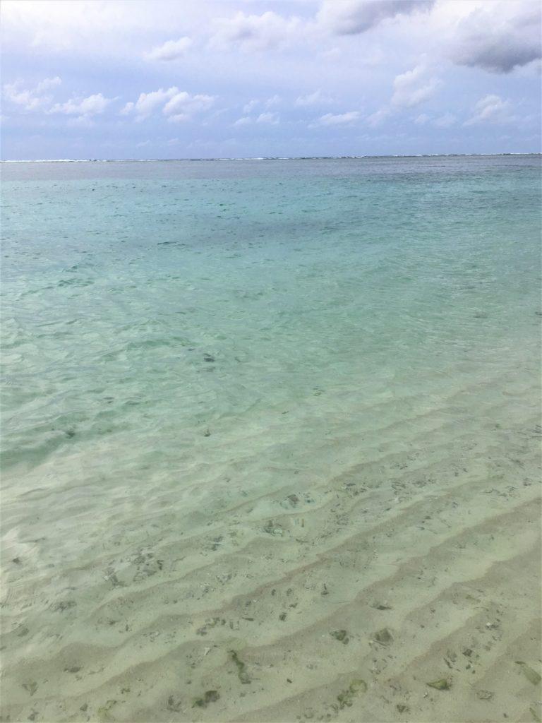 淡いブルーが綺麗なタモンビーチの波打ち際を撮影した写真