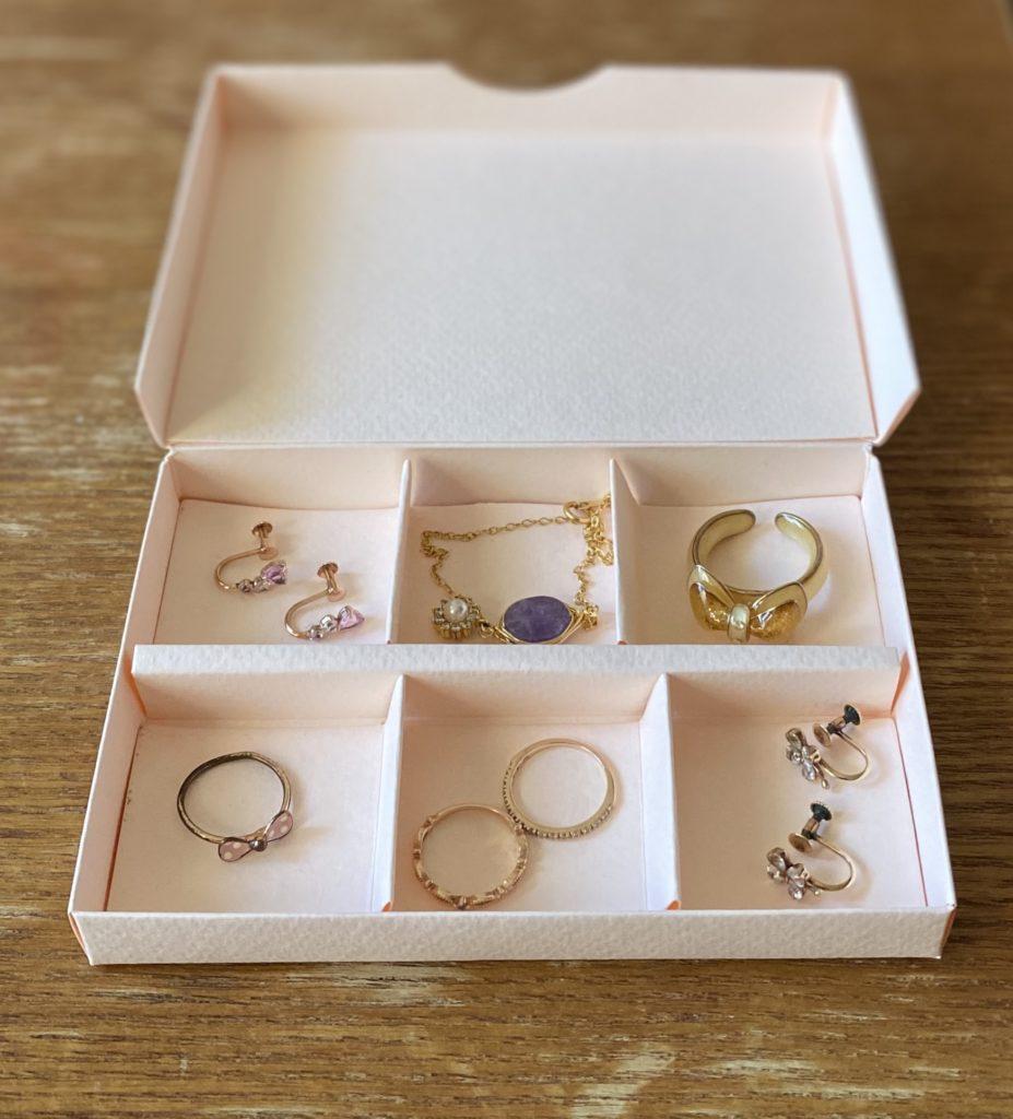 フェーヴァ・ダナンでチョコレートを買ったときに併せて購入した専用ボックス(淡いピンク色)をアクセサリーケース代わりに使用している様子を撮影した写真