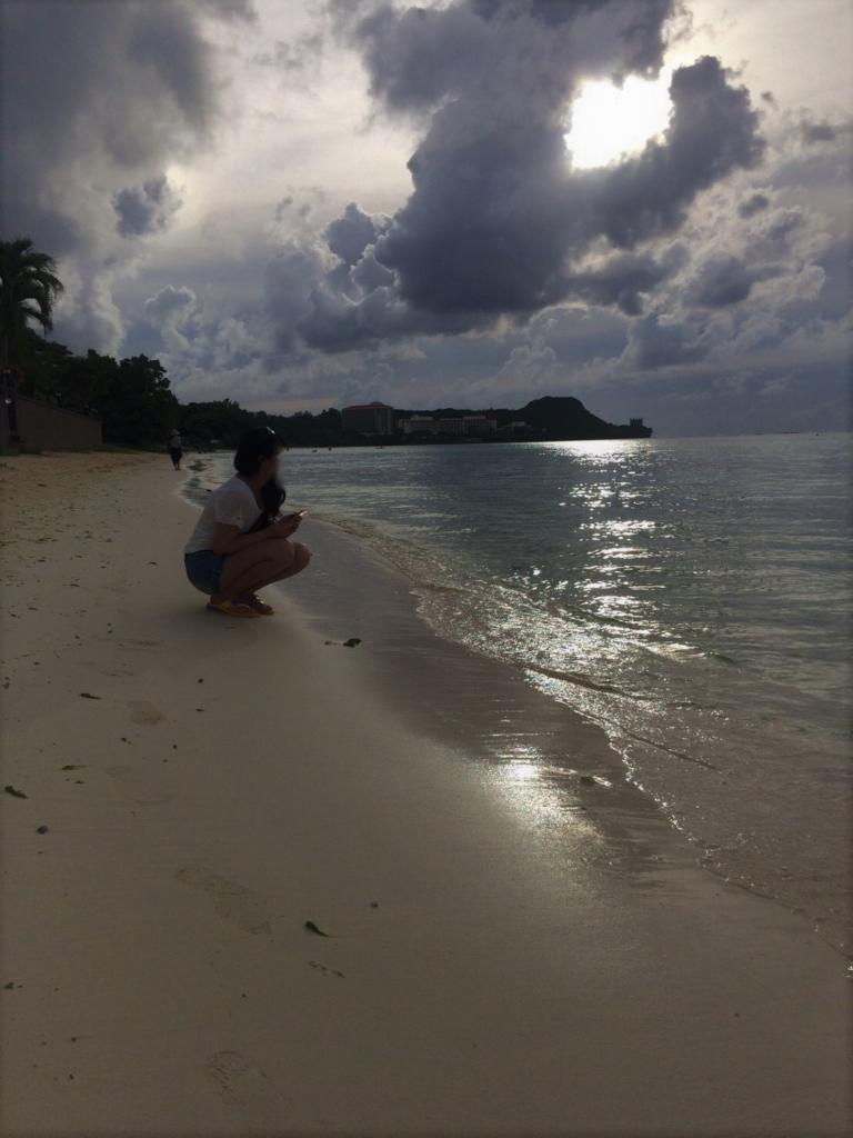 私が、砂浜で夕日を眺めている様子を撮影した写真