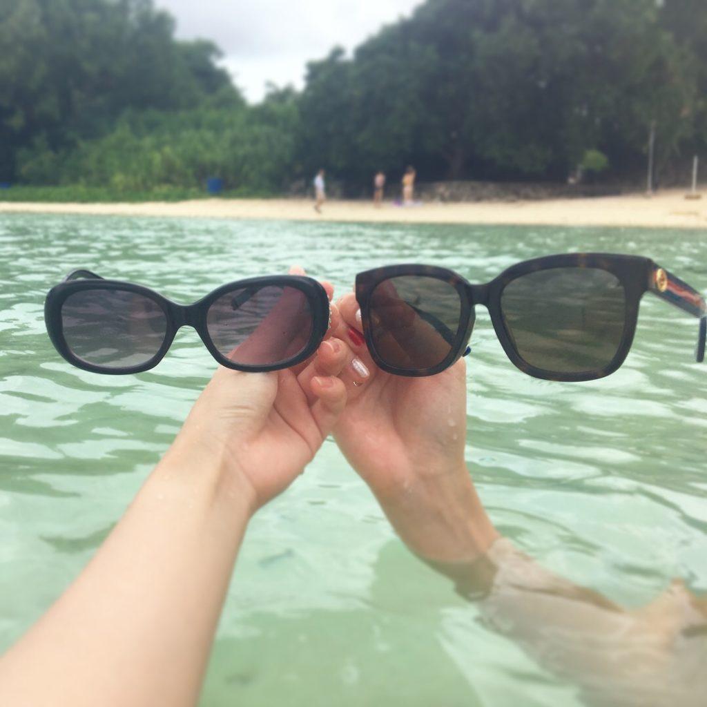 グアムの海に浸かって2人でサングラスを映して楽しんでいる様子
