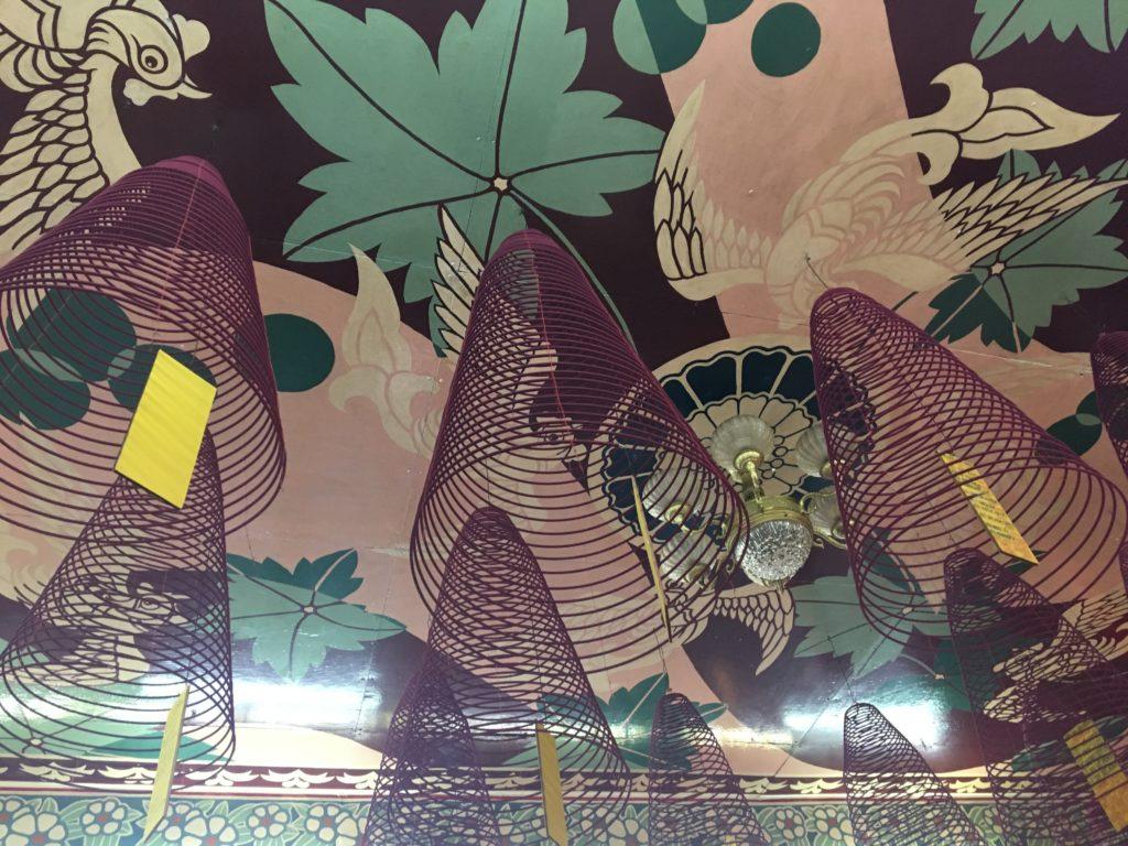 福建会館で見た、模様が描かれた天井から螺旋線香がいくつもつるされている様子を撮影した写真