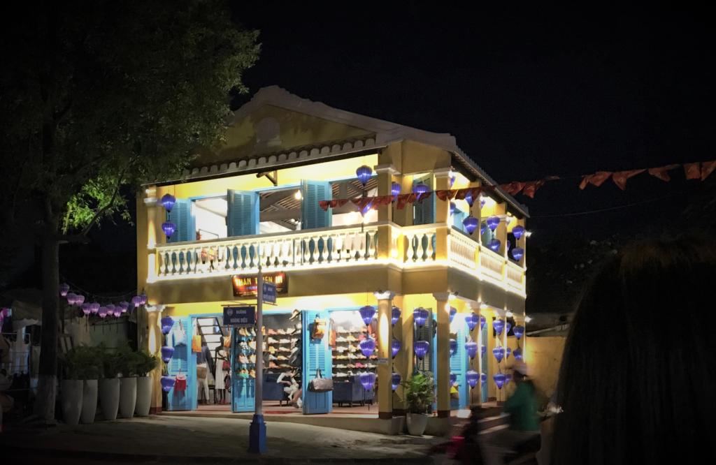 グエンズイヒエウ通りとホアンジェウ通りの交差点で見かけた、ライトアップされたブルーとパープルのランタンが黄色いお店に映えている様子を撮影した写真