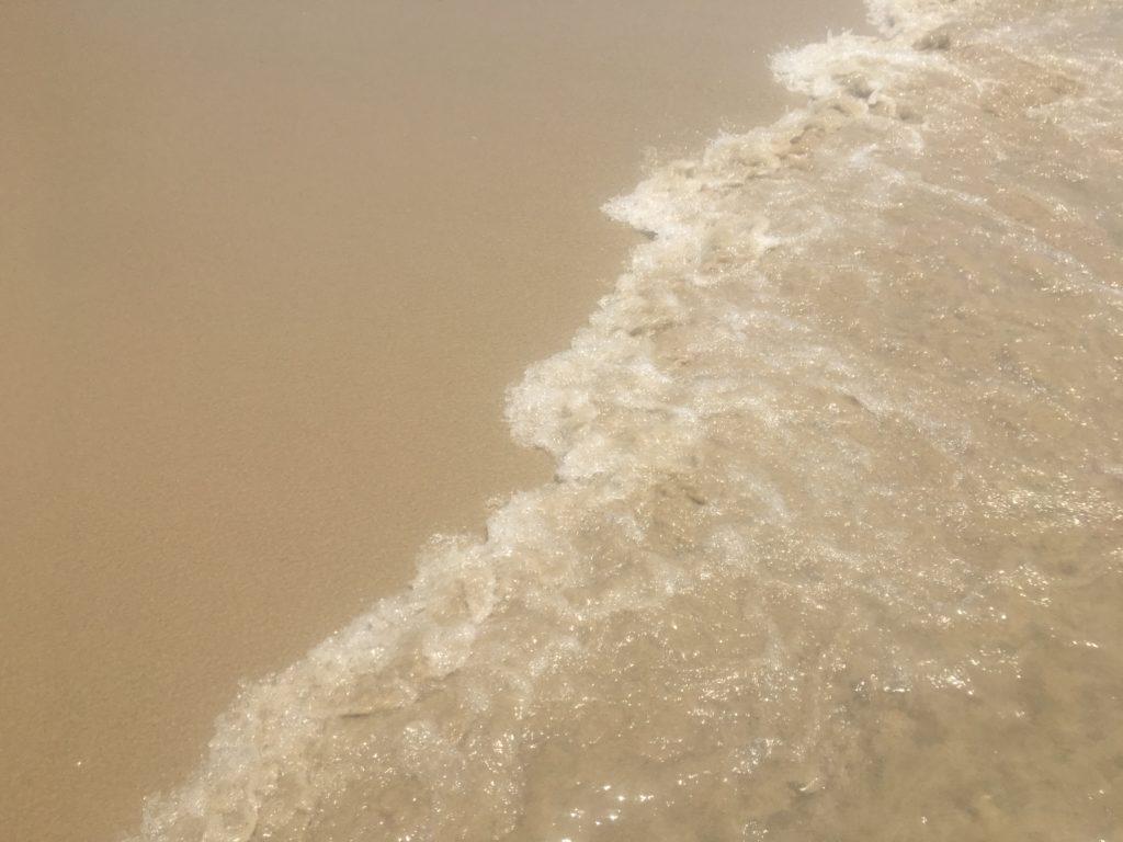 ミーケービーチの砂浜に透明度の高い波が打ち寄せる様子を撮影した写真