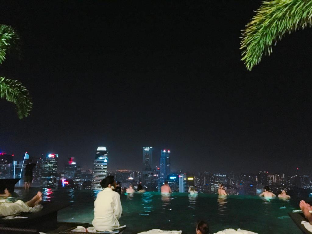 夜間の込み合っているインフィニティプールを撮影した写真