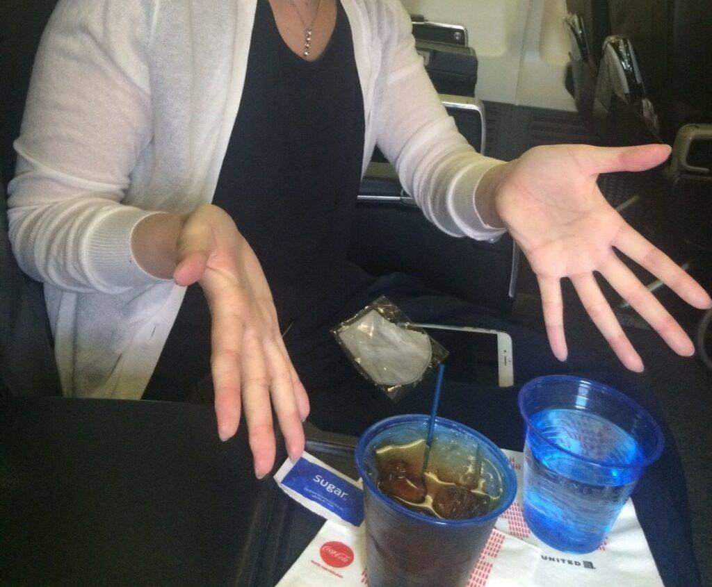 ユナイテッド航空ビジネスクラスで、隣の席との間のスペースにドリンクを置いている様子を撮影した写真