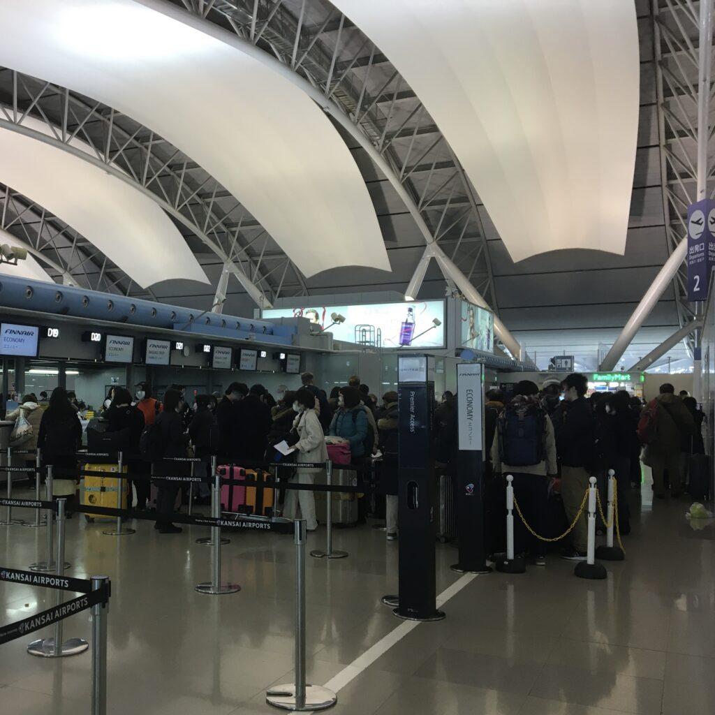 関西国際空港のフィンエアーエコノミークラスのチェックインカウンターに並んでいる人々の手前に、ユナイテッド航空プレミアアクセス専用の優先チェックインカウンターがある様子(別の旅行時に見たもの)を撮影した写真